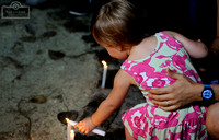 A young girl lights a candle in memory to the Paris victims.